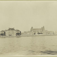 Another view of Ellis Island from the harbor, but showing a ...