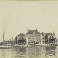 Another view of Ellis Island from the harbor, showing variou...