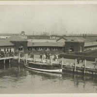 Buildings near Ellis Island pier; immigrants can be seen wit...