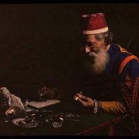 Costumed man examining jewelry (pawnbroker?)