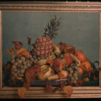 Still life study, bowl of fruit behind gold frame
