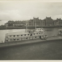 View of Ellis Island buildings and two ferries at pier; appa...