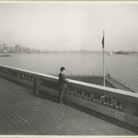 A derby-topped gentleman observing the harbor form the obser...