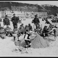 British, French and American soldiers seated with W.A.A.C.s on the sands watching French kiddies building sand castles