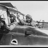 Cheery pilot and observer with their mascot pup ready for a flight over the German lines