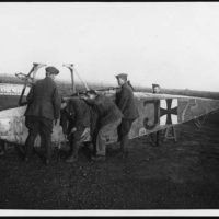 Flying Corps men lifting the body of a Boche plane which we brought down