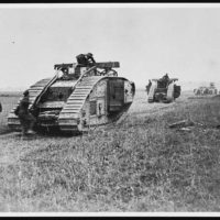 Tanks passing dead Germans who were alive before the cavalry advanced a few minutes before the picture was taken
