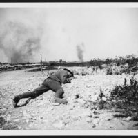 To save himself from the flying shrapnel of the two high explosive shells that have burst near, this Tommy has flung himself flat on the ground