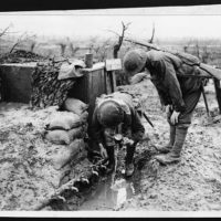 Two men of the Coldstream Guards having a drink from a forward water supply