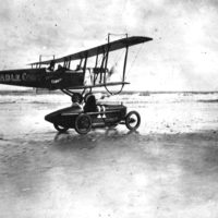 Pilot for the Mabel Cody Flying Circus holds steady    as Bugs McGowan transfers from the car to the plane