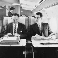 Two men on Northwest Airlines aircraft, one using typewriter, with female flight attendant in background