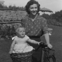 Woman pushing a bicycle with a baby riding in a basket - 13